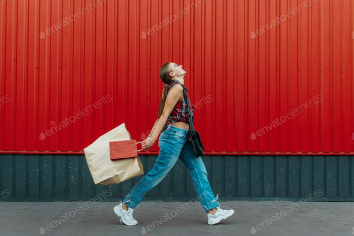 Happy girl with shopping paper bag on red wall shop background. Young woman holding shopping bag