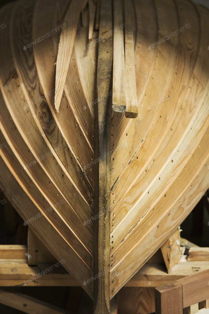 Close up of a wooden boat hull in a boat-builder's workshop.