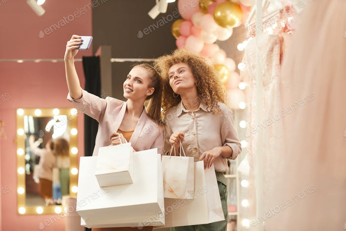 Two Young Women Taking Selfie in Mall