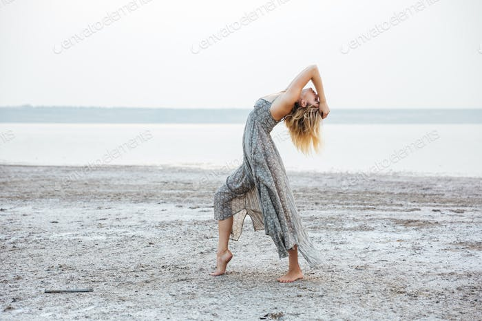 Pretty young woman in dress dancing barefoot on the beach
