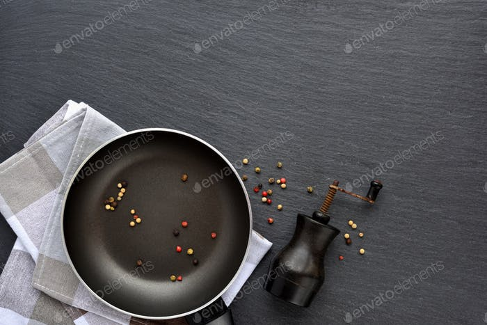 Empty frying pan with mix peppers and vintage mill on dark grey