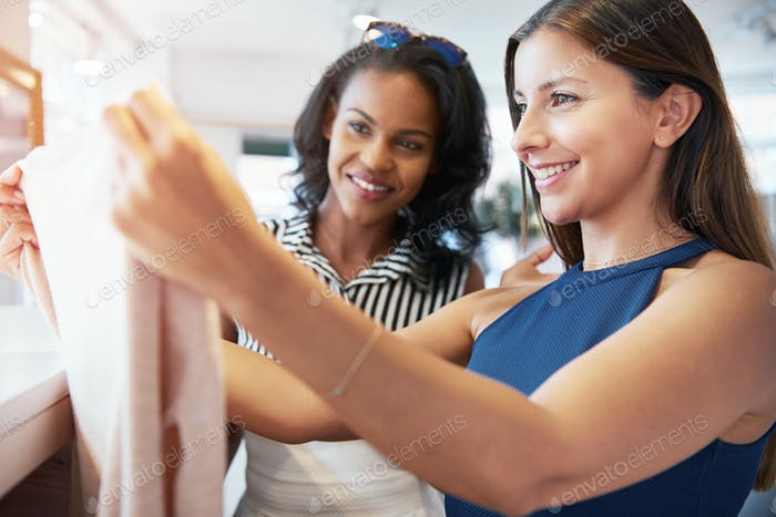Zwei junge weibliche Freunde kaufen für Kleidung