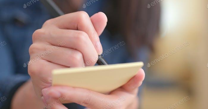 Frau notiert einige Notiz auf Memo