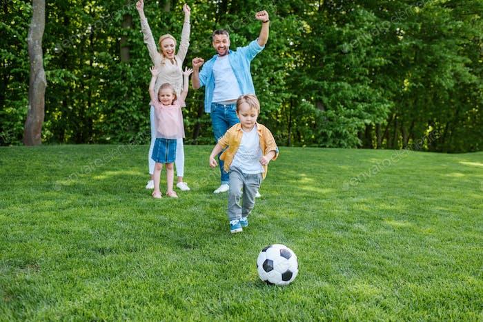 glückliche Familie spielt mit Fußball im Park