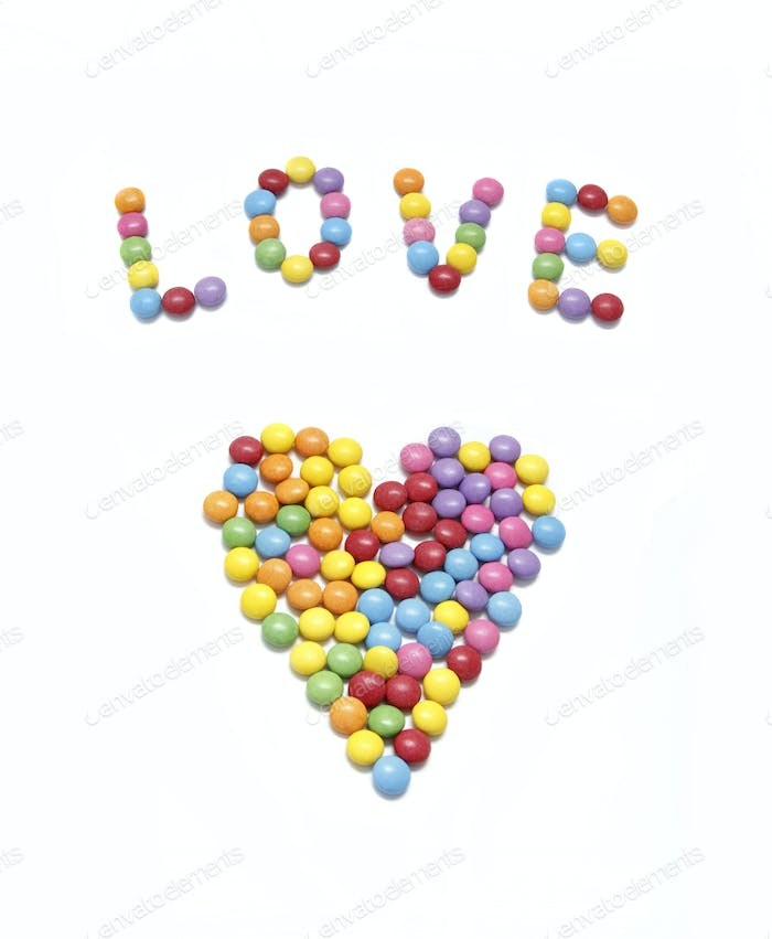 Word LOVE and abstract heart from bright colorful candy