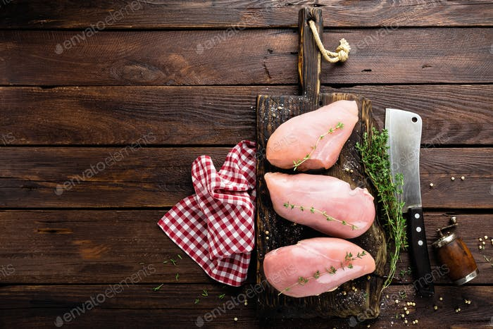 Raw chicken meat fillet on wooden background