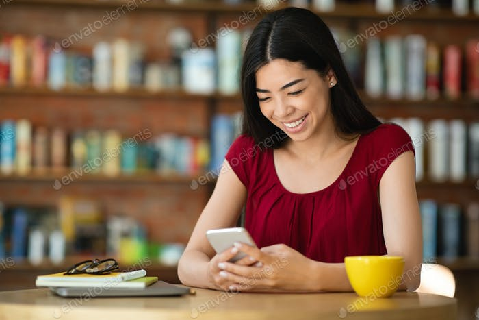 Smiling Asian Girl Messaging On Smartphone During Coffee Break In City Cafe