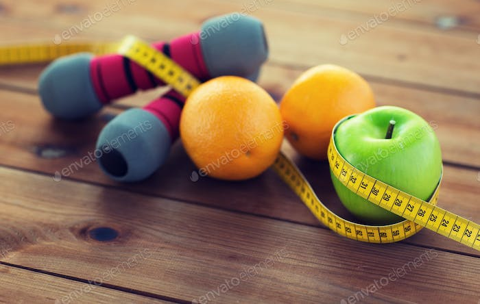 close up of dumbbell, fruits and measuring tape