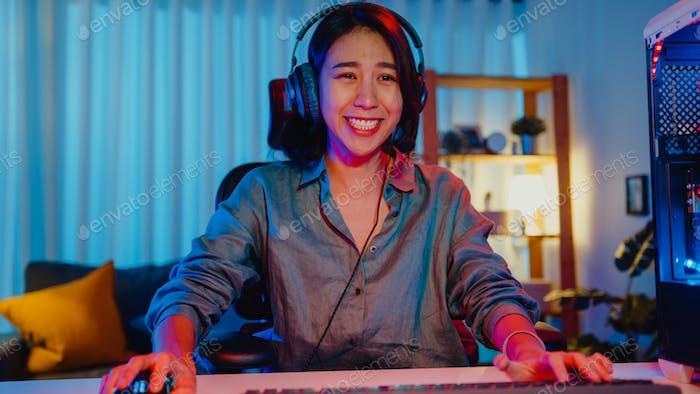 Happy asia profesional chica jugador desgaste auriculares participación jugar videojuego.