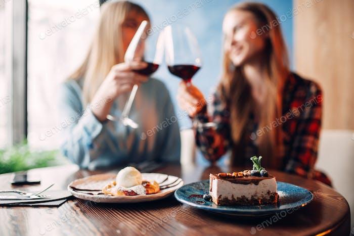 Girlfriends drinks red wine and eats dessert