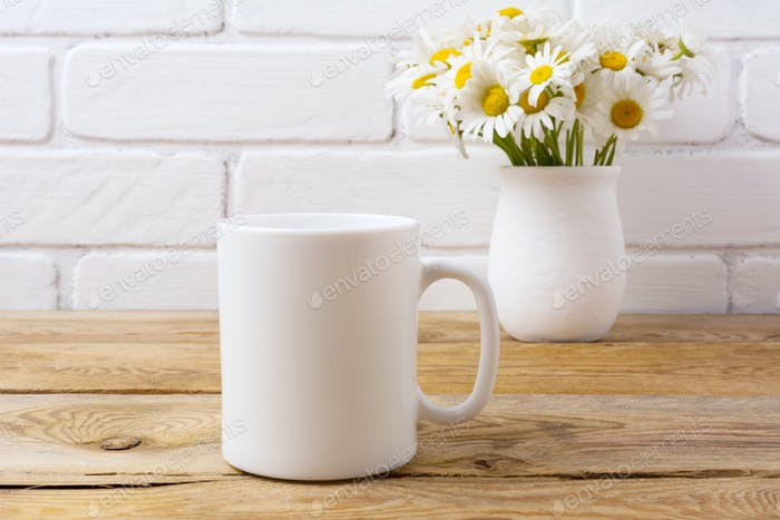 White coffee mug mockup with chamomile bouquet in rustic vase