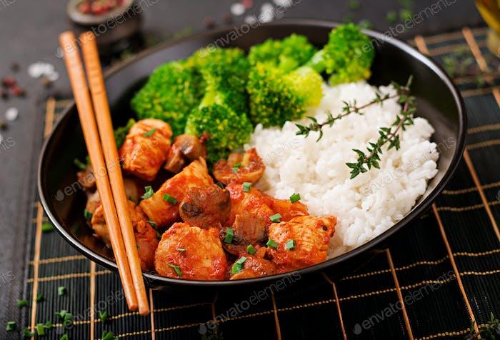 Stücke von Hähnchenfilet mit Pilzen in Tomatensauce mit gekochtem Brokkoli und Reis gedünstet