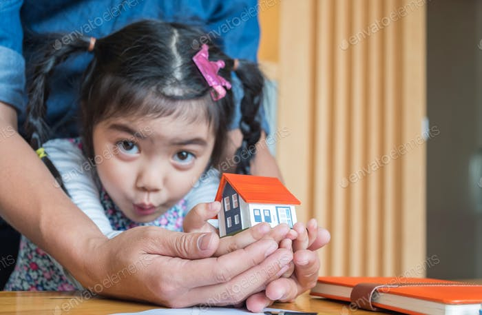 Father and daughter Use your hand to hold the house model.