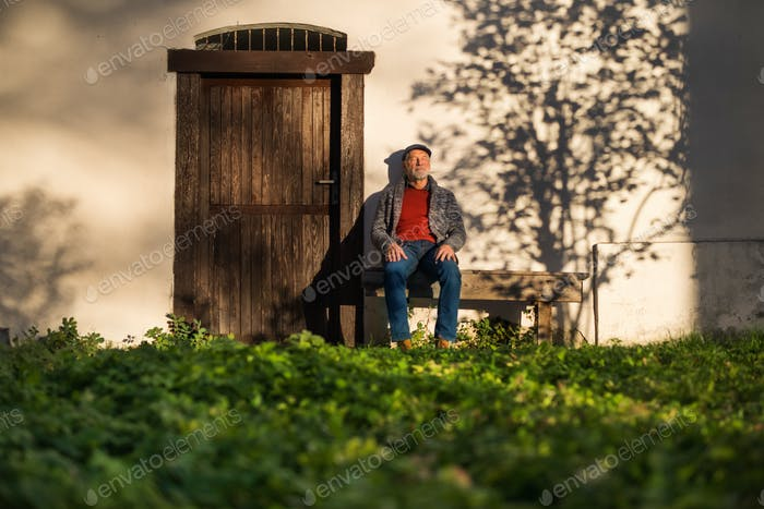 Lonely senior man sitting on bench in front of old house, eyes closed