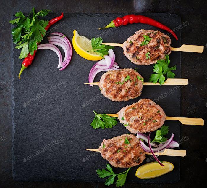 Appetizing kofta kebab (meatballs) on black background. Top view