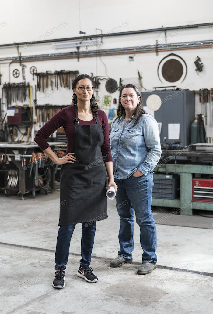 Two women wearing apron and Denim shirt standing in metal workshop, smiling at camera.