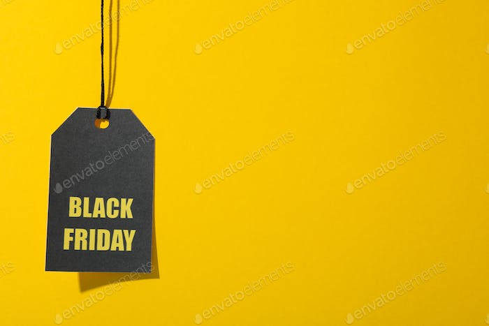 Inscription Black Friday on price tag on yellow background, copy space