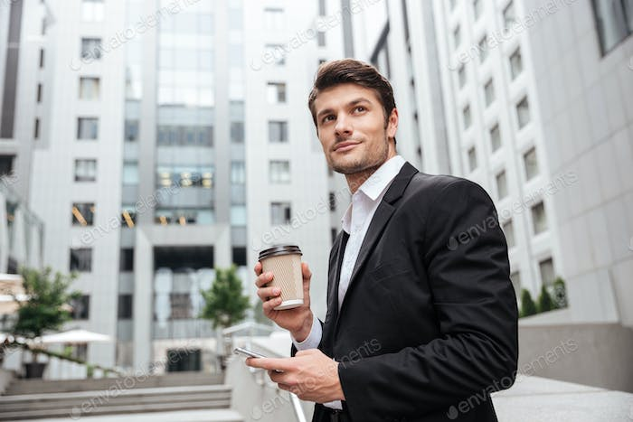Businessman with take away coffee standing and using mobile phone