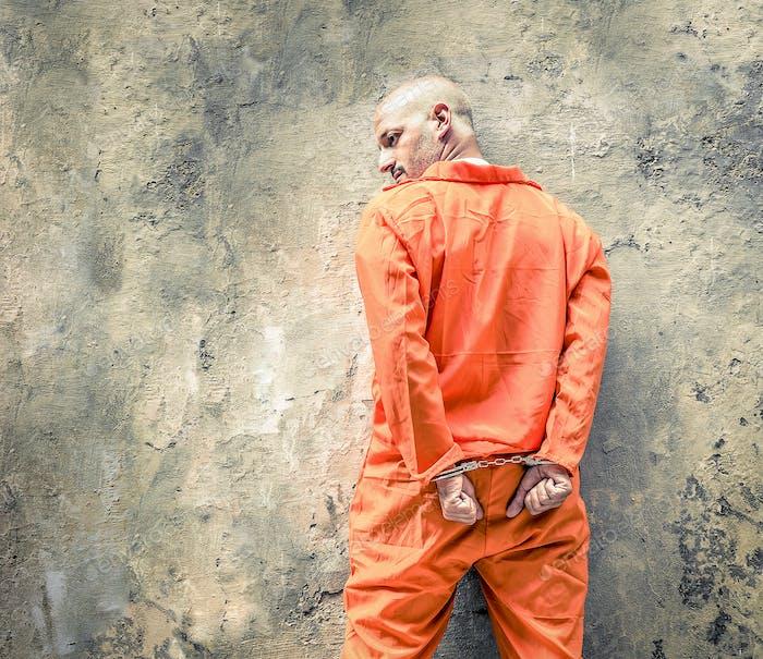 Handcuffed prisoners waiting at jailhouse wall
