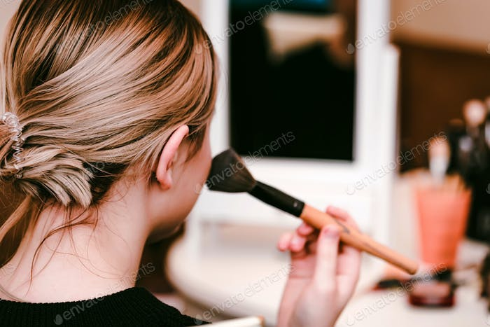 Back view teenage girl applies makeup with brush
