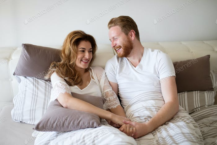 Happy married couple being romantic and sensual in bed