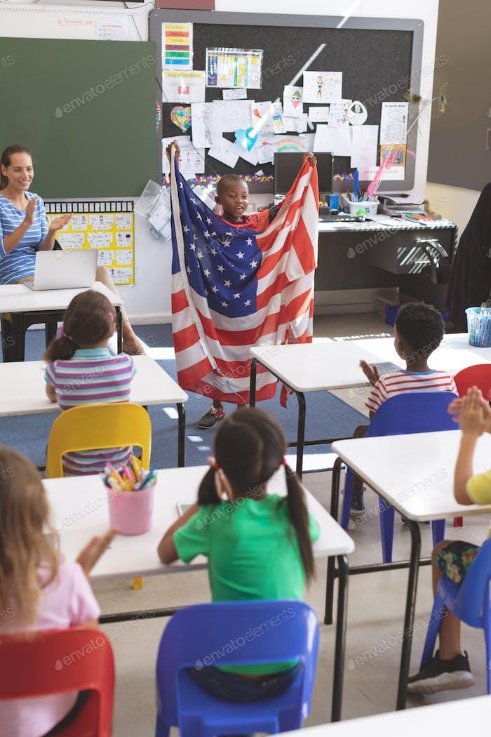 Schoolboy mit amerikanischer Flagge im Klassenzimmer in der Schule