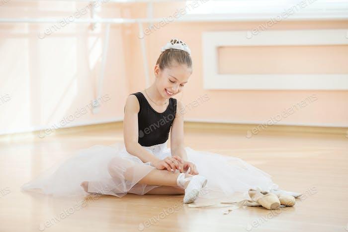 Junge Balerina wechseln Tanzschuhe zu zeigen, während sie auf dem Boden sitzen