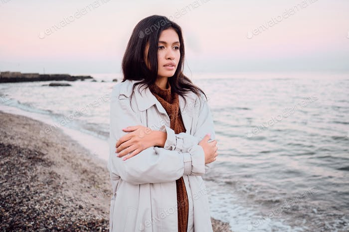 Beautiful stylish Asian brunette girl in trench coat trying warm up dreamily walking by the sea