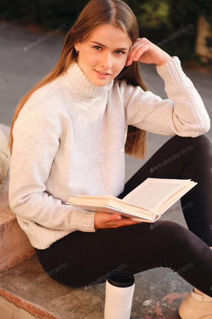 Beautiful student girl in cozy sweater happily looking in camera studying with textbook outdoor