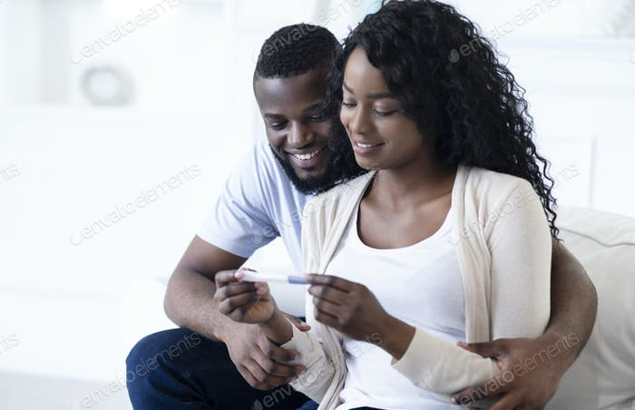 Young black couple happy about positive results of pregnancy test