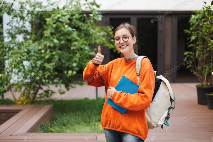 Pretty smiling lady in eyeglasses standing with backpack and showing big thumb up