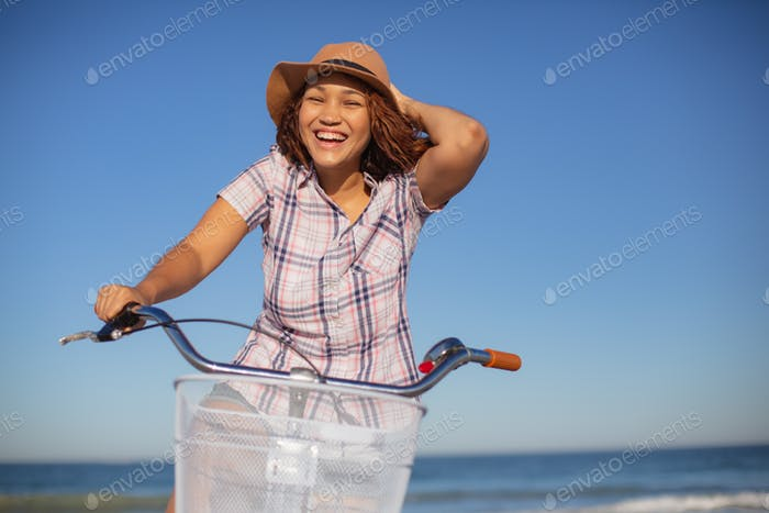 Front view of beautiful mixed race woman sitting on bicycle at beach in the sunshine