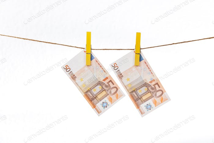 Euro banknotes are attached with yellow clothespins to a rope on a white background
