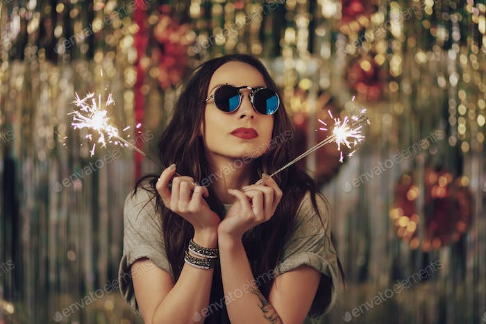 Attractive hipster girl holding sparklers in hands