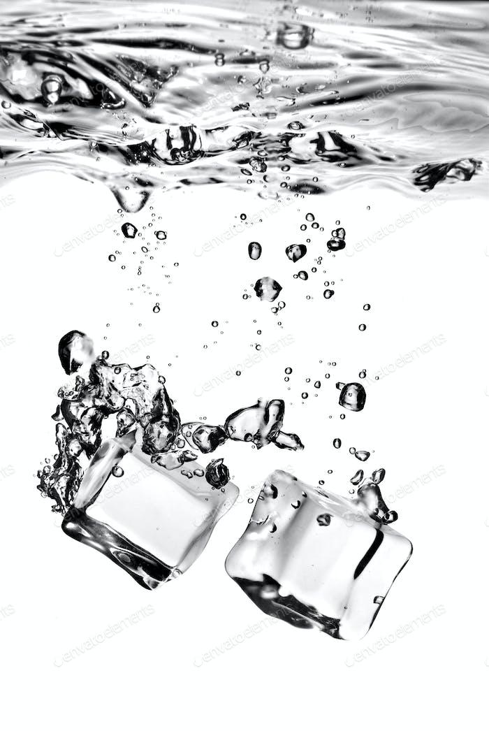 Eiswürfel in Wasser mit Spritzer auf weiß isoliert fallen