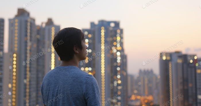 Человек смотрит на небоскреб под закатом