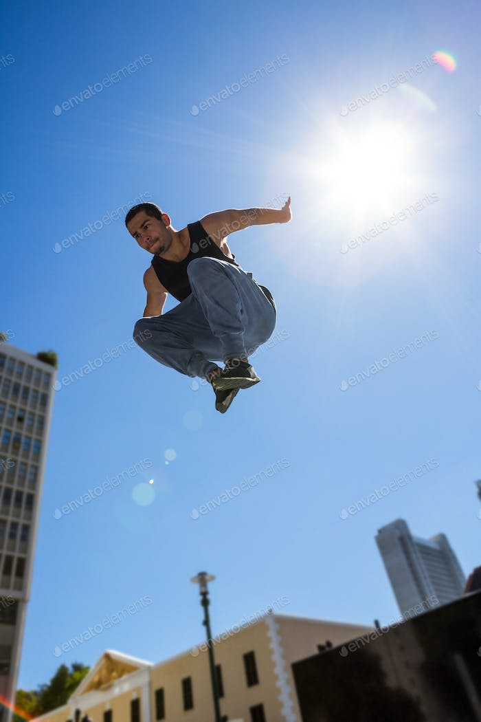 Man doing hardcore parkour in the city on a sunny day