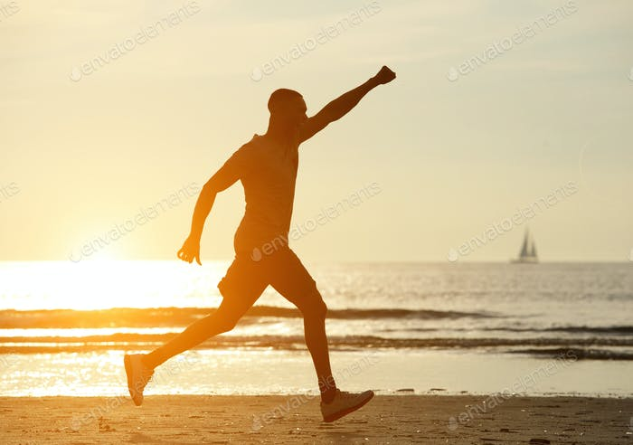 One man running on beach with hand raised