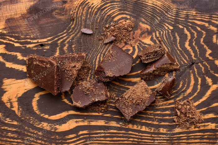 Pieces of chocolate on dark wooden background. Top view