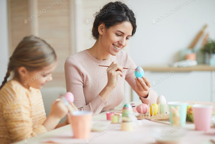Smiling Young Woman Painting Easter Eggs at Home