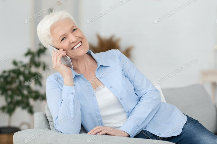 Mobile Communication Concept. Cheerful Elderly Lady Talking On Cellphone At Home