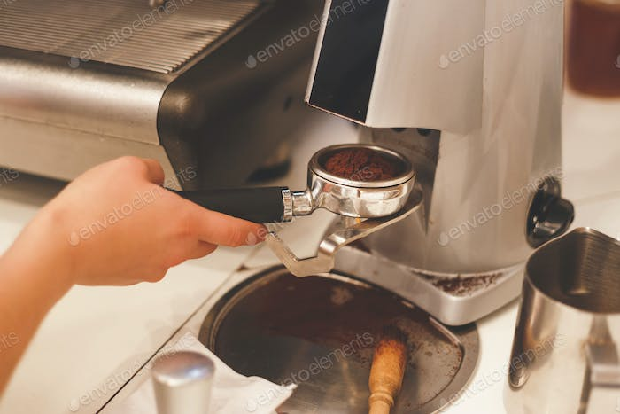 Freshly ground coffee in the portafilter into the hands of a professional barista