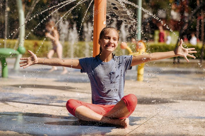 Little girl sitting in yoga pose, water playground