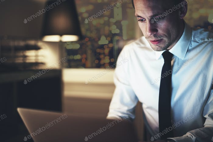 Serious businessman working on laptop