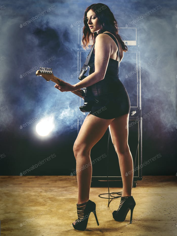 Beautiful woman with red hair playing electric guitar