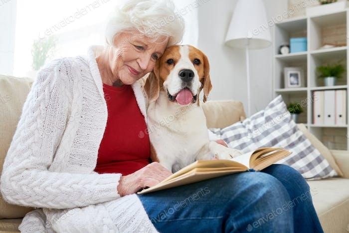 Lächelnde Senior Frau Lesbuch mit Hund