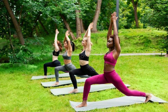 Multinationale junge Mädchen praktizieren Yoga im Freien, stehen in Krieger-Pose im Park. Freier Speicherplatz