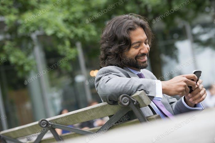 Мужчина в деловом костюме с полной бородой и вьющимися волосами. Использую его телефон.
