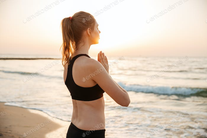Woman meditating on the beach at sunset