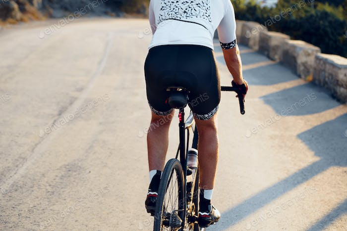 Close-up of men's sports ass in shorts riding a bicycle